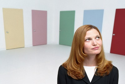 Woman in front of six doors unable to decide which door to use, illustrating analysis paralysis.