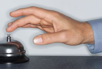 Image of hand ringing a concierge bell depicting the need for customer service in I.T.