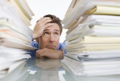 Image of distraught man behind a mountain of papers depicting the need to manage staff burnout.