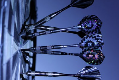 Image of darts on a dartboard representing the need to not make project assumptions.