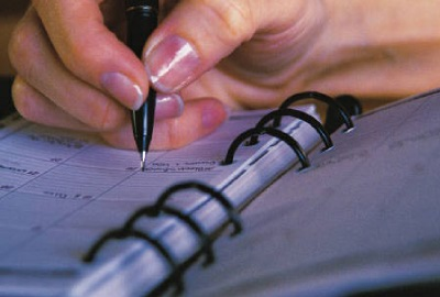 Image of business woman writing in her appointment book signifying the need for proper scheduling strategies.