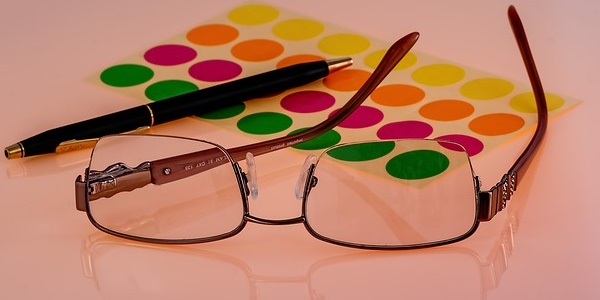 Image of eyeglasses, pen and colored tabs signifying the need for IT strategic vision.