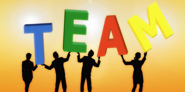 Image of four people holding up the letters 'TEAM', depicting the need to evaluate team performance.