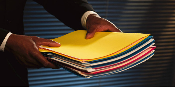 Image of man in a suit holding out a stack of file folders signifying that he intends to delegate the work.