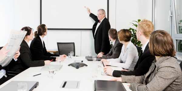 Image of a project team in a conference room discussing project committee conduct.