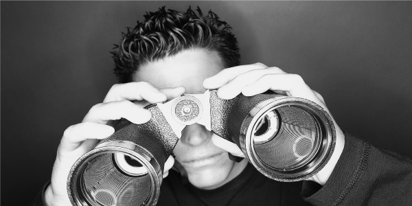 Image of man looking through binoculars depicting the need to perform a post meeting assessment.
