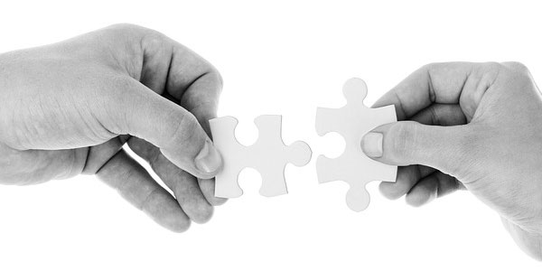 Image of two hands, each holding a puzzle piece signifying the need to employ project job descriptions.