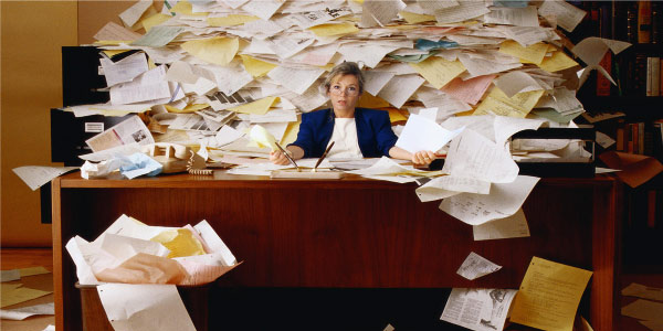 Image of woman at a desk in front of mountain of papers depicting the need to be ready for risky projects.