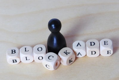 Image of chess piece with building blocks spelling out 'blockade' depicting barriers to productivity.