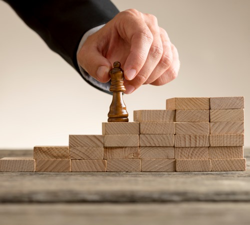 Person placing chess piece on a stack of blocks signifying the basics of disaster recovery planning.