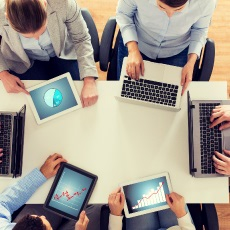 Team of people at table with computers signifying the need and use for a meeting agenda.