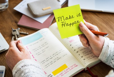 Person working on to-do list with note 'make it happen' signifying the need to motivate project teams.
