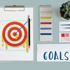 Image of target on wall with a sign 'goals' depicting the need for project technology standards.