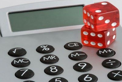 Image of desk calculator with a pair of dice on it conjuring the costs of downtime.