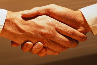 Image of two businessmen in shirt sleeves shaking hands depicting the need to apologize if you are in customer service.