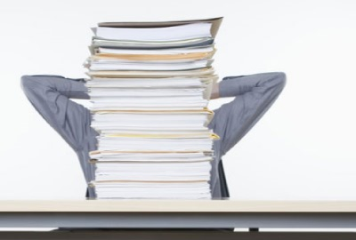 Image of person sitting behind a towering stack of papers punctuating the need for project document management.